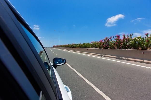 Automobile sulla strada con il fondo del mosso