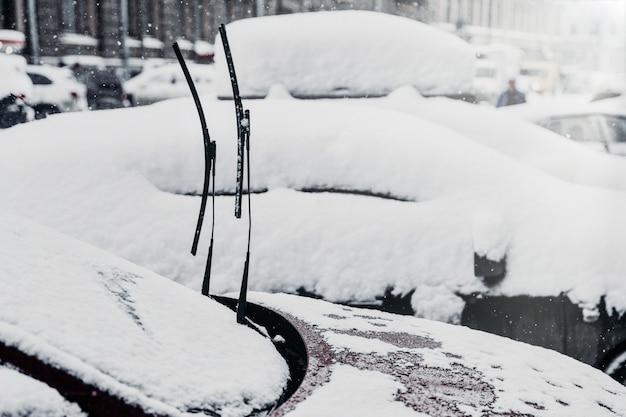 Automobili coperte di neve spessa dopo nevicate, vetro ghiacciato, clima invernale