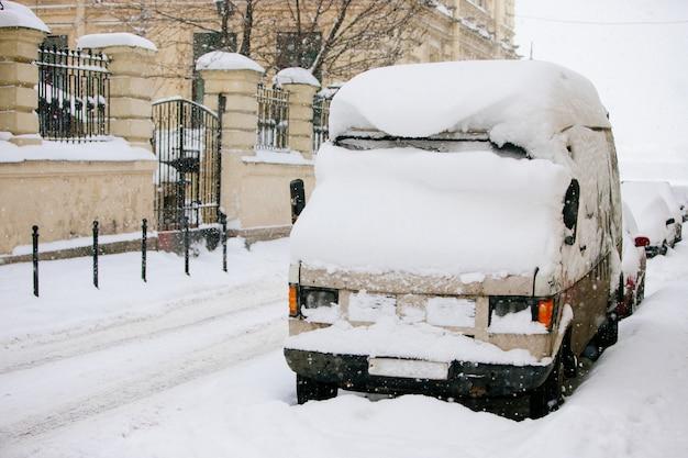 Automobili parcheggiate coperte di neve dopo la tempesta di neve