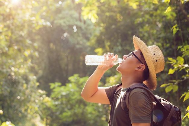 Autostoppista asiatico dell'uomo che prende una pausa per bere dalla bottiglia di acqua mentre facendo un'escursione al fondo della natura