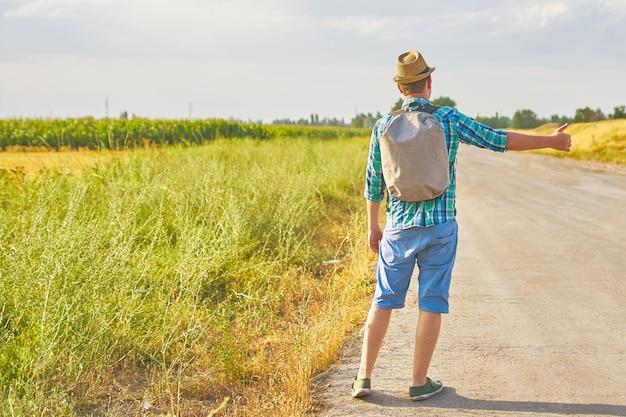 Autostoppista con zaino in cappello estivo, camicia leggera, pantaloncini sulla strada in campagna tropicale