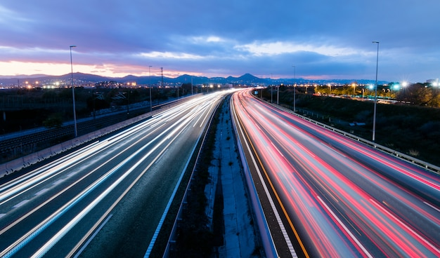 Autostrada al tramonto, veicoli che guidano in due direzioni lasciando tracce di luce