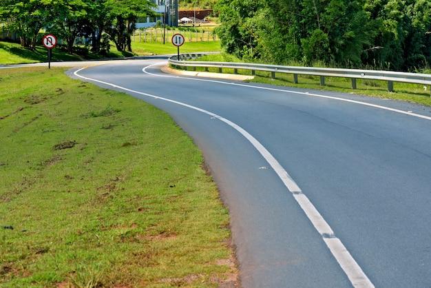 Autostrada tortuosa con campi verdi all'orizzonte