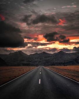 Autostrada vuota con vista montagna sotto il cielo scuro