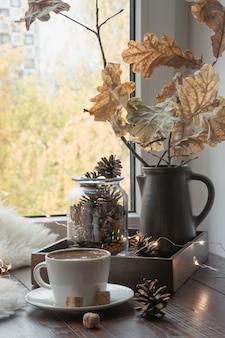 Autunno accogliente natura morta sul davanzale della finestra a casa interna. tazza di caffè a casa calda in soffice pelliccia. hygge.
