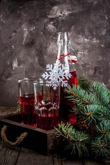Autunno, bevande invernali. succo di mirtillo rosso fatto in casa, in una bottiglia e bicchieri su un vecchio tavolo rustico in legno, con rami di albero di natale e decorazioni, copia spazio