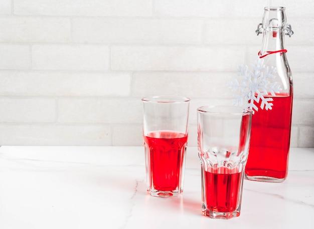 Autunno, bevande invernali. succo di mirtillo rosso fatto in casa, in una bottiglia e bicchieri sul tavolo di marmo bianco. copia spazio