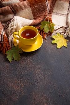 Autunno con una tazza di tè, plaid e foglie