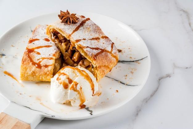 Autunno domestico, cottura estiva, sfogliatine. strudel di mele con noci, uvetta, cannella e zucchero a velo. sul tavolo di marmo bianco. affettato, con gelato e topping al caramello. copyspace