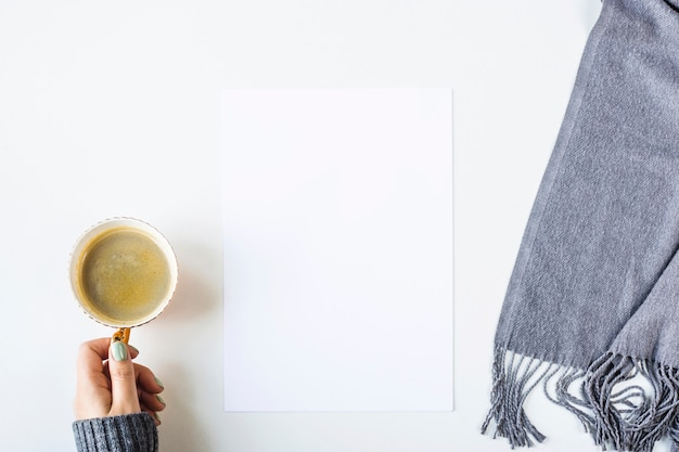 Autunno mock up su un tavolo bianco accanto a una sciarpa e una tazza di caffè
