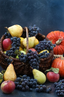 Autunno natura morta con mele, uva, zucca e pere situate su uno sfondo scuro, vendemmia autunnale, mele, pere e uva nel cestino