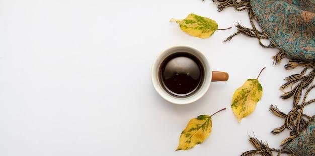 Autunno piatto disteso con caffè, foglie cadute e una sciarpa.