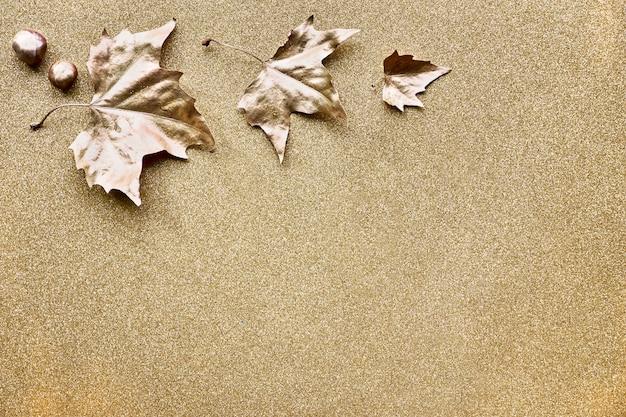 Autunno piatto disteso con foglie dipinte in oro e copia-spazio su scintillante pape dorato