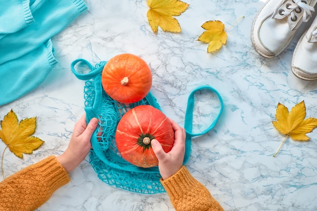 Autunno piatto disteso con mani femminili che mettono la zucca arancione nel sacchetto di stringa turchese. vista dall'alto su sfondo di marmo bianco con scarpe bianche, maglione e foglie gialle.