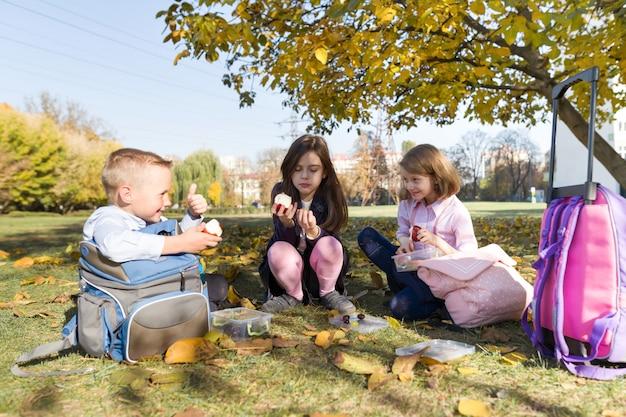 Autunno ritratto di bambini con scatole per il pranzo, zaini scuola