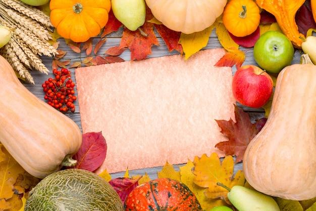 Autunno sfondo del ringraziamento con zucche, segale, melone, mela, pera e fogliame colorato su carta vintage.