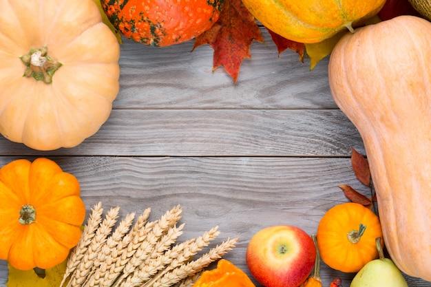 Autunno sfondo del ringraziamento con zucche, segale, melone, mela, pera e fogliame colorato sul tavolo di legno. vista dall'alto con spazio di copia per il testo