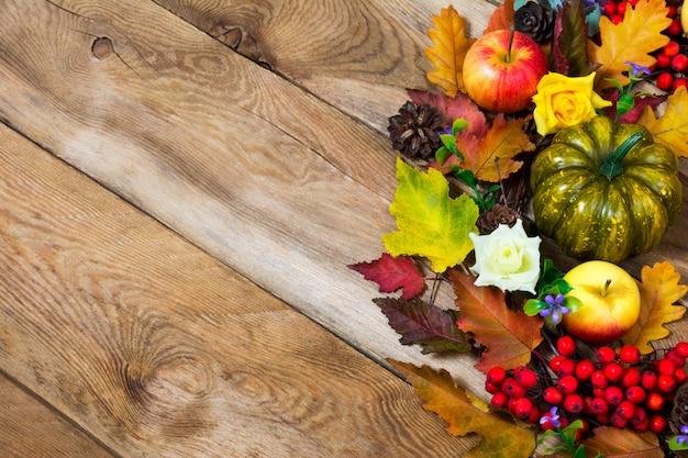 Autunno sfondo rustico con foglie colorate caduta, zucca verde, mela, fiori lilla e bacche rosse, copia spazio