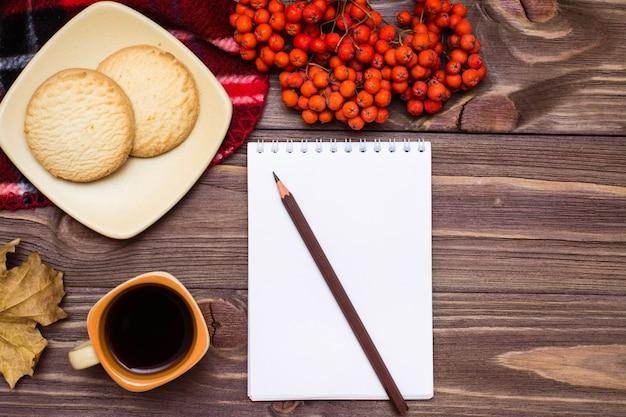 Autunno still life caffè, biscotti, un plaid, un quaderno e una matita su legno vista dall'alto