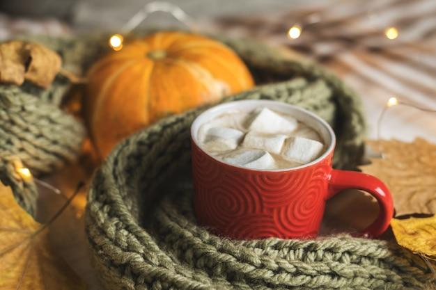 Autunno still life di zucca, foglie, sciarpa, tazza rossa di cacao con marshmallow