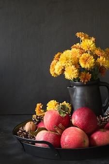 Autunno still life. raccolto di caduta con le mele, fiori gialli in vaso su oscurità.