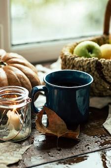 Autunno, tè, zucche e mele su un tavolo di legno