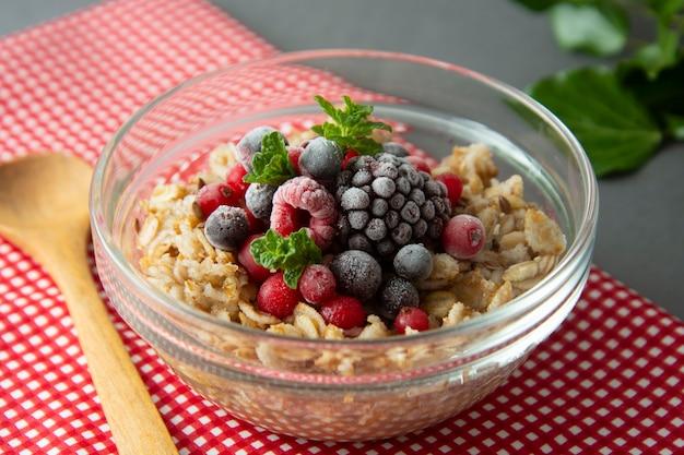 Avena colazione sana, frutti di bosco congelati, fragole fresche, menta.