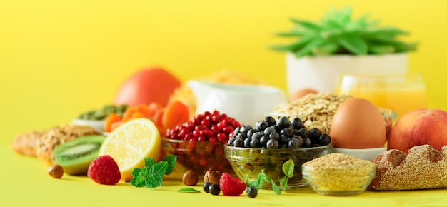 Avena e fiocchi di mais, uova, noci, frutta, bacche, pane tostato, latte, yogurt, arancia, banana, pesca