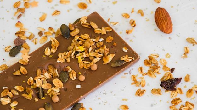 Avena e frutta secca sulla barretta di cioccolato su sfondo bianco