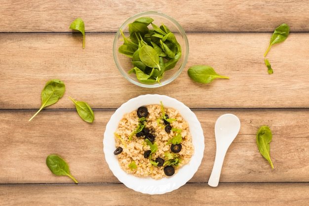 Avena guarnita con foglie di basilico e olive per colazione in una ciotola