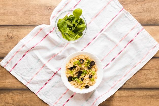 Avena sano guarnito con foglia di basilico e oliva per colazione sul tavolo di legno