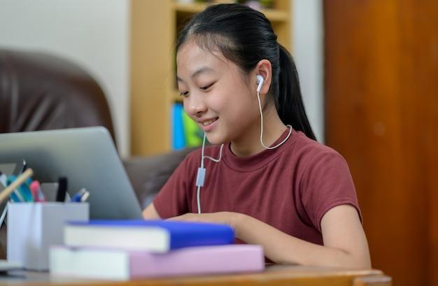 Avere lezione online. i bambini asiatici studiano da soli con l'e-learning a casa. formazione in linea e studio autonomo e concetto di homeschooling.