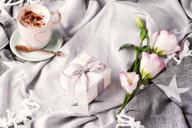 Avere una tazza di caffè con cioccolato, confezione regalo e fiori eustoma sulla coperta nel letto.