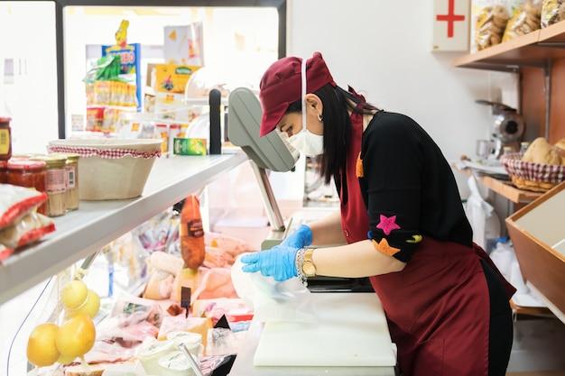 Avetrana, italia, - marth 16, 2020. la commessa sta servendo un cliente una mozzarella, indossando maschera medica e guanti protettivi durante l'epidemia di coronavirus. shopping, pandemia di covid-19