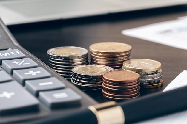 Avings, finanze, economia e casa - vicino su del calcolatore che conta soldi e che prende le note a casa