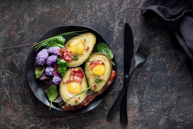Avocado al forno con uovo e pancetta, piatto giaceva sul tavolo scuro