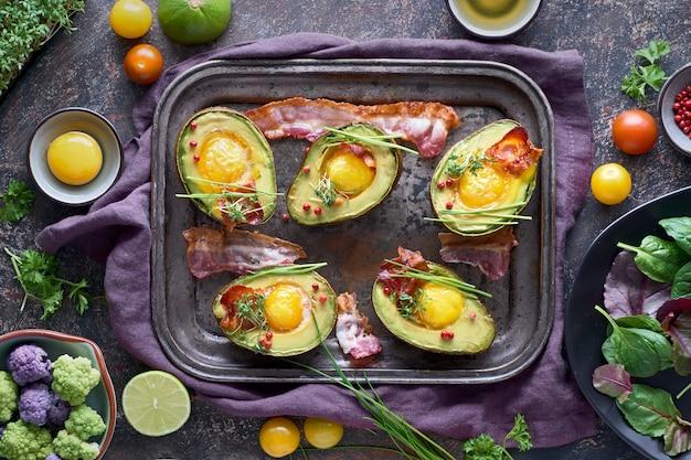 Avocado al forno con uovo e pancetta su una teglia di metallo, piatto giaceva con ingredienti ed erbe su oscurità