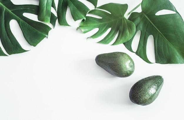 Avocado con foglie tropicali su sfondo bianco