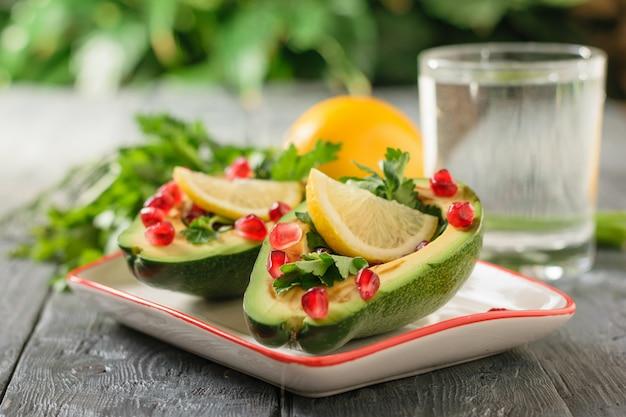 Avocado con semi di melograno, salsa balsamica, limone ed erbe e bicchiere d'acqua sul tavolo nero