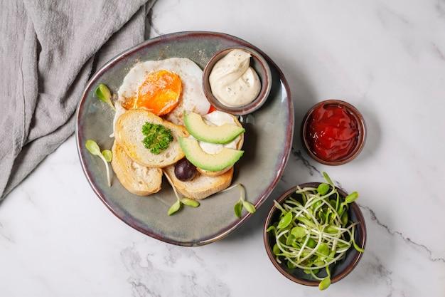 Avocado e sandwich con uovo fritto. avocado affettato albero ed uovo fritto su pane tostato per la prima colazione.