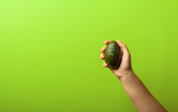 Avocado in una mano di donna verde muro. concetto di cibo sano