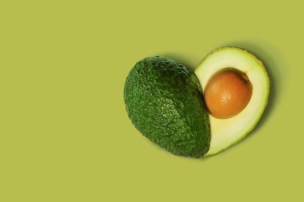 Avocado isolato su verde a forma di cuore