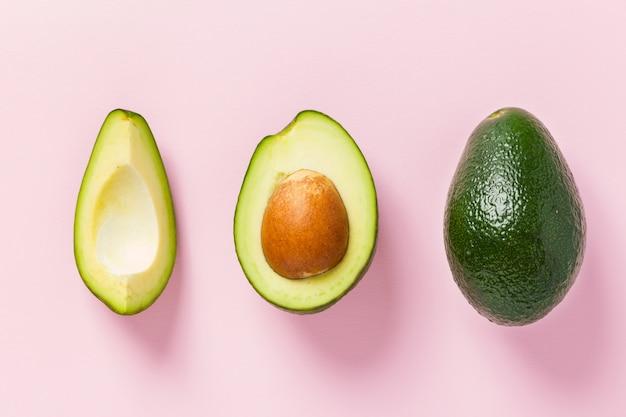 Avocado maturo su fondo rosa - intero e frutta verde fresca del taglio con il seme su pastello