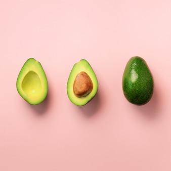 Avocado organico con semi, metà di avocado e frutti interi su sfondo rosa. modello di avocado verde in stile minimal piatto laico.