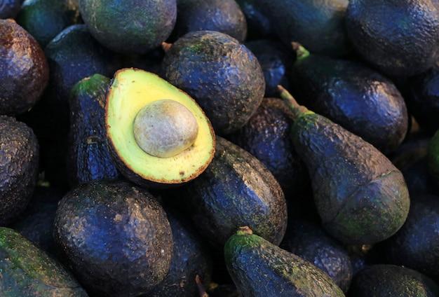 Avocado tagliato a metà su sfondo avocado.