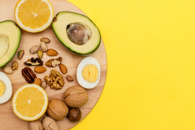 Avocado, uova, limone, noci sul tagliere di legno. concetto di cibo sano. dieta chetogenica piatta.