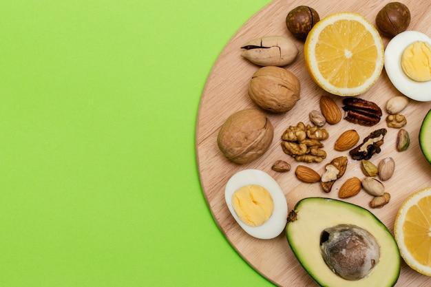 Avocado, uova, limone, noci sul tagliere di legno. concetto di dieta chetogenica.