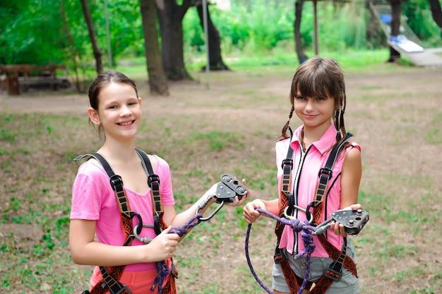 Avventura arrampicata su un parco ad alto filo - facendo un'escursione nel parco della corda due ragazze
