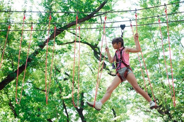 Avventura che scala il parco di alto cavo - facendo un'escursione nella ragazza del parco della corda