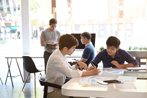 Avviare giovane riunione di brainstorming di affari sulla scrivania dell'ufficio